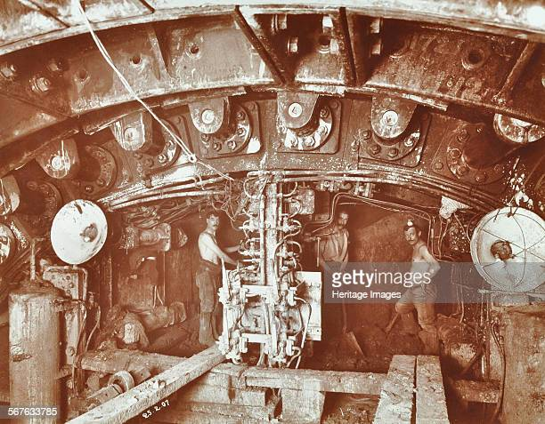 Miners at work on the construction of the Rotherhithe Tunnel Bermondsey London February 1907 Two sections of the shield with barechested miners at...
