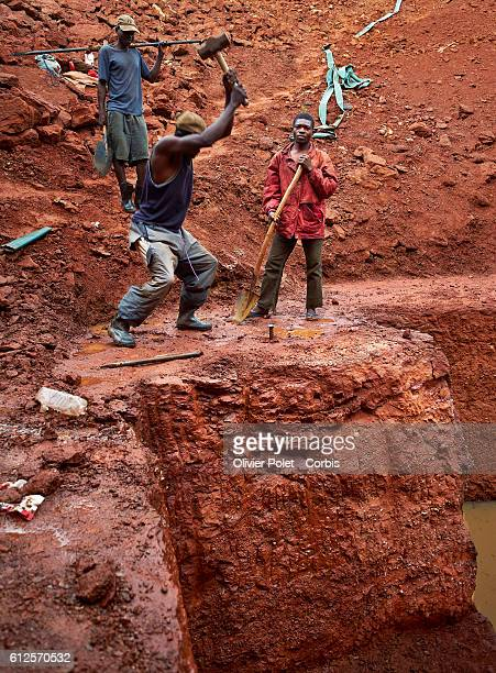 Miners break the rich rock layer prior to sifting it 28 March 2013 in in search of diamonds near an Angolan village not far from the Congolese border...