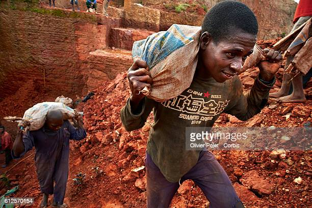 Miners carry bags filled with excess earth 28 March 2013 to clear the concession and expose the diamondrich layers near an Angolan village not far...