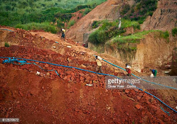 Miners carry bags filled with excess earth out of his concession surrounded by hoses pumping out the rain water from their plots 28 March 2013 near...