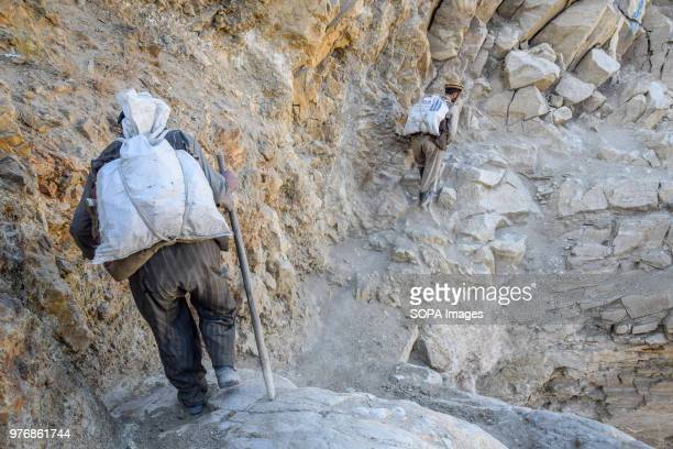 Miners carrying heavy bags filled with lapis lazuli down the mountain from the mine. Over the past years the government embargoed what it deems to be...