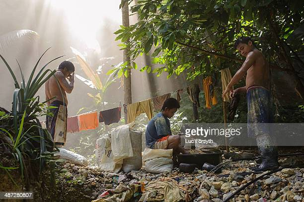Miners check themselves for mud after showering during their mid day break on April 22 2014 in PinutAn Philippines Muddy and wet tunnel conditions...