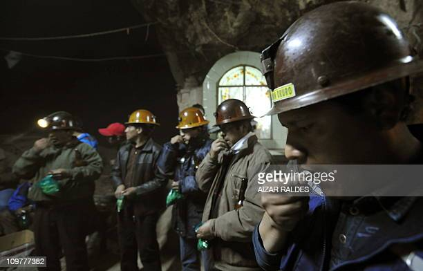 Miners chew coca leaves as they perform the traditional Challa sacrifice ceremony in honour of the Pachamama at the Hitos tin mine on the outskirts...