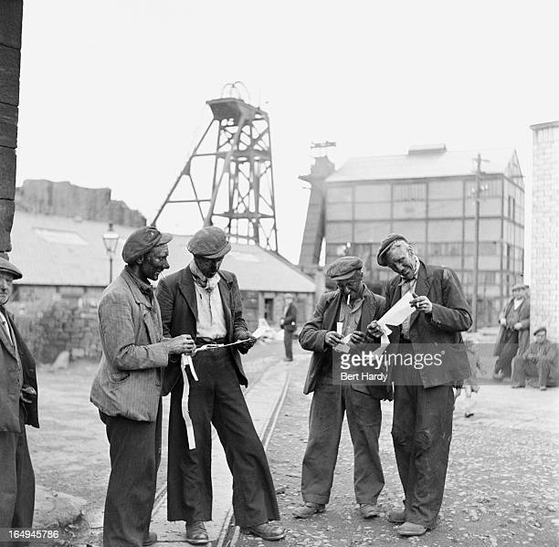Miners compare wage slips after a shift at Heworth Colliery near Newcastle Tyneside October 1950 Original publication Picture Post 5138 Down The Tyne...