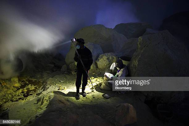 Miners extract lumps of sulfur from the Ijen volcano at night in Banyuwangi East Java Indonesia on Thursday June 2 2016 Sulfur isn't an easy material...