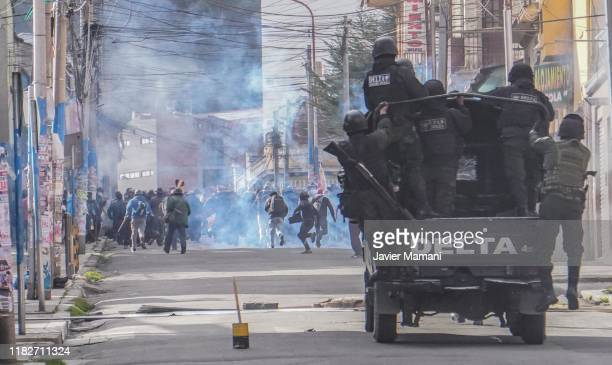 Miners from Colquiri receive tear gas from police during a protest on November 15, 2019 in La Paz, Bolivia. Morales flew to Mexico alleging a coup...