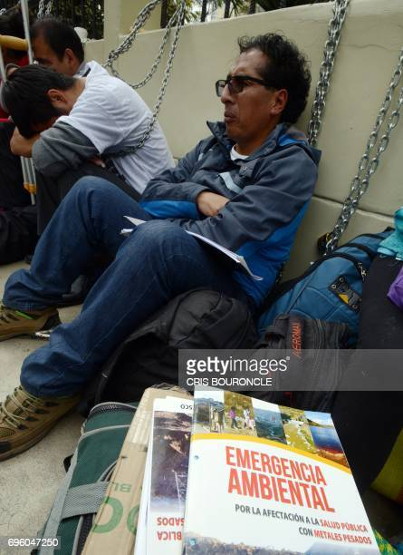 Miners from near Pasco Peru and their relatives remain chained to the fence of the building of the Ministry of Health in Lima during a protest in...