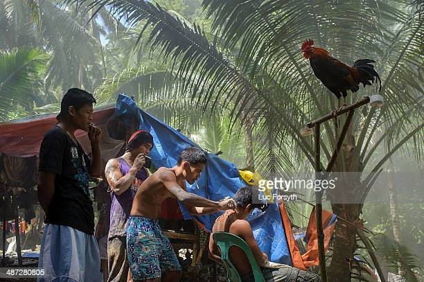 Miners gather around to watch a haircut in their mountainside camp at the end of a day's work on April 22 2014 in PinutAn Philippines Gold mining is...