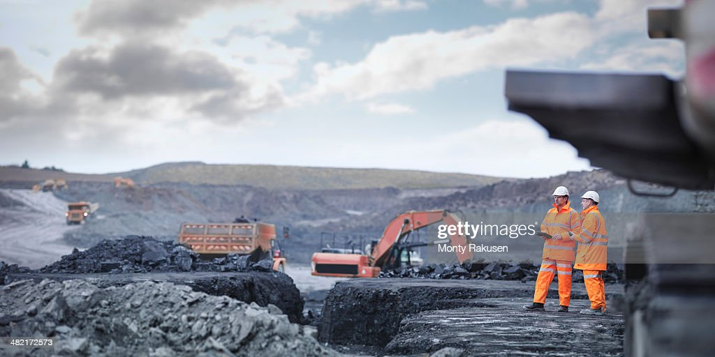 Miners in discussion in surface coal mine : Stock Photo
