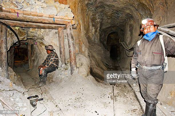 Miners in the tunnels of the old Candelaria silver mine in Potosi . The black pipes running along the wall of the gallery are for compressed air...