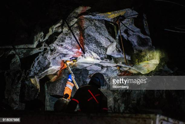 Miners insert steel reinforcement rods into the rock face inside a mine shaft at the Northam Platinum Ltd Booysendal platinum mine located outside...