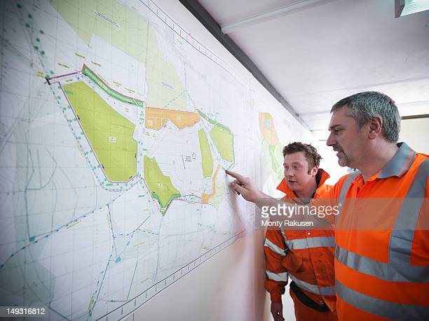 Miners inspect map in opencast coalmine
