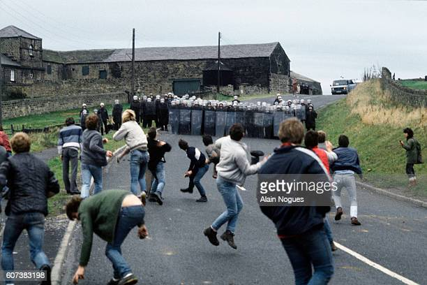 Miners pick up and throw stones at state police forces on a country road in Woolley. English coal miners had struck for eight months. | Location:...