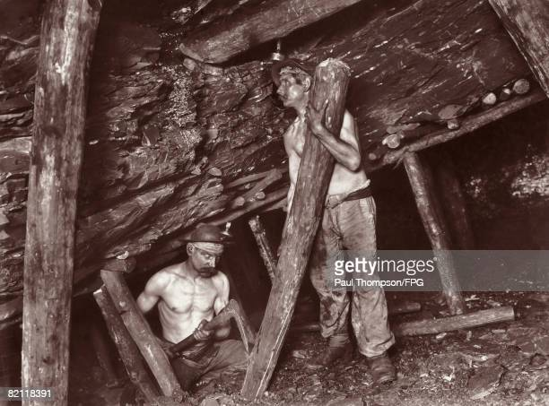 Miners place pit props in position in an Italian coal mine circa 1900