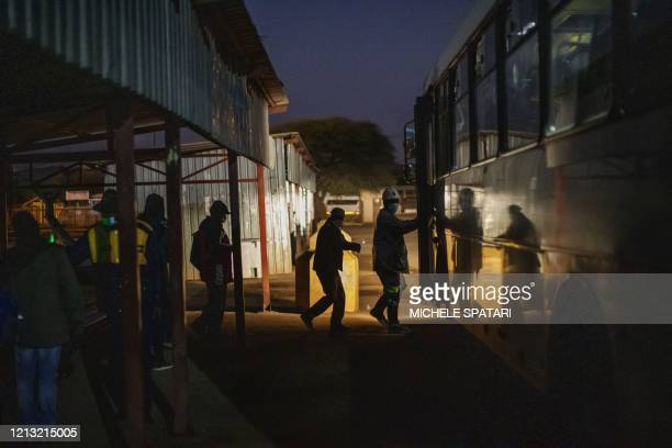 Miners queue to board a company bus en route to the evening shift at the SibanyeStillwater platinum mine in Marikana Rustenburg on May 15 2020 after...