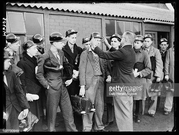 Miners receiving their helmets and boots 1944 A photograph of a group of 'Bevin Boy' miners receiving their equipment on their first day at Askern...