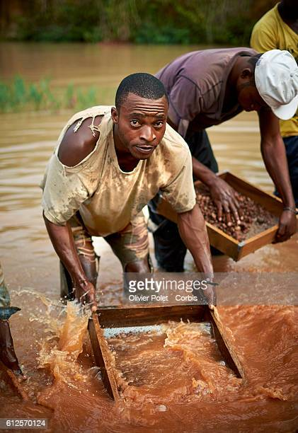 Miners sift through the selected rich rock fragments 28 March 2013 in search of a diamond gem near an Angolan village not far from the Congolese...
