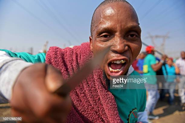 Miners sing and chant gather during an event to commemorate the sixth anniversary of the Marikana massacre on August 16, 2018 in Rustenburg, South...