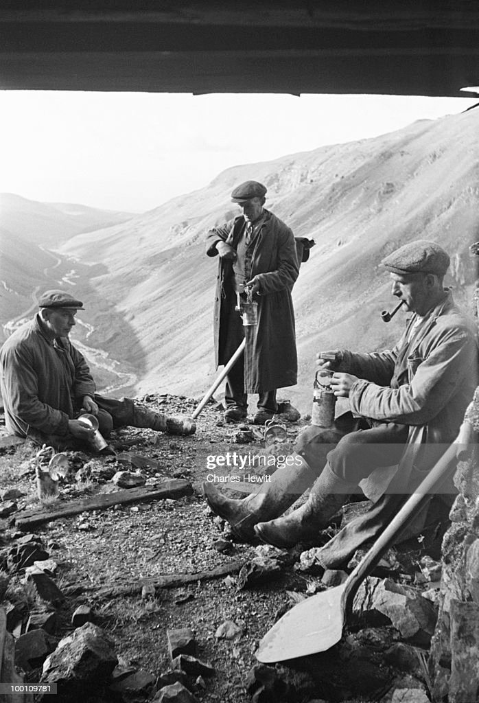 Miners sitting outside the entrance to a baryte drift mine on the border between Westmorland and County Durham, February 1949. Original publication: Picture Post - 4712 - Britain's Loneliest Mine - 5th February 1949