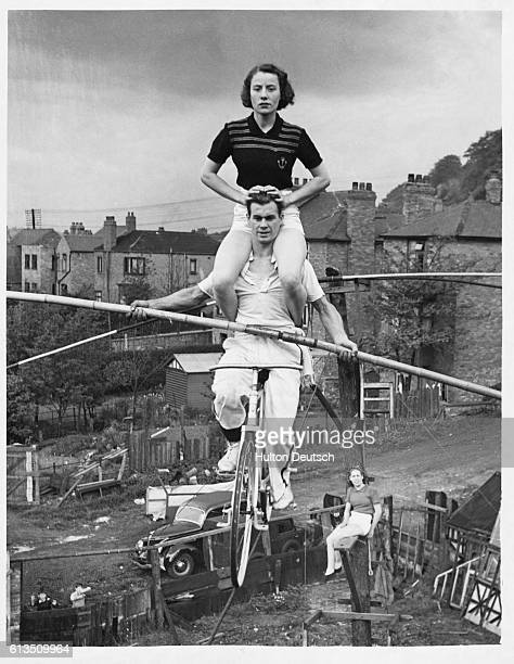 Miner's son Harold Davis rides his bicycle along the tightrope in the back garden while his sister Elsie sits on his shoulders The family group of...