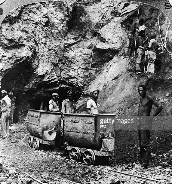 Miners stand by two mine cars on their track at one of the De Beers mines Kimberley South Africa early 20th Century