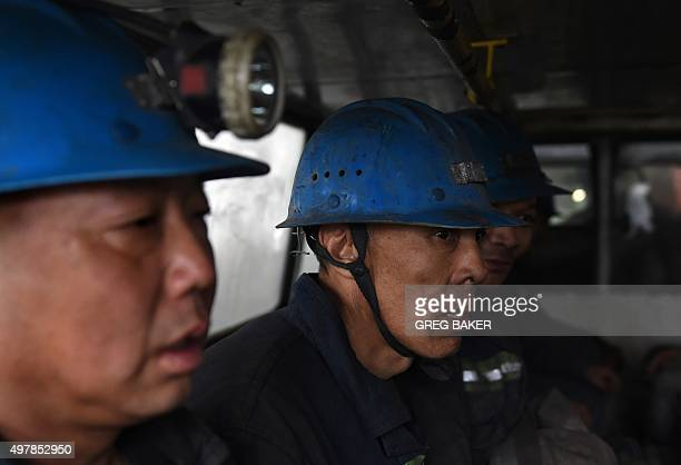 Miners wait on a bus before being driven into a coal mine near Datong in China's northern Shanxi province on November 19 2015 China will not improve...