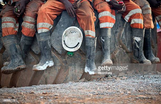 Miners wear rubber safety boots while sitting on a rock above ground before returning to the digging face for their afternoon shift at the Gara gold...