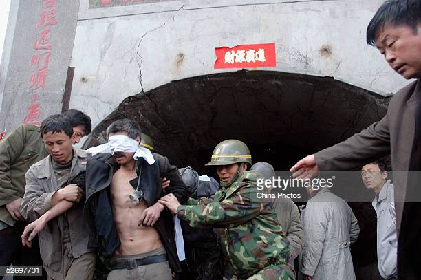 Miners whose eyes are protected by cloth from light come out of a flooded coal mine after they were rescued on April 25 2005 in Jiaohe County of...