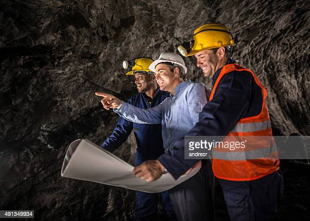 miners working at the mine with an engineer - underground mining stock photos and pictures