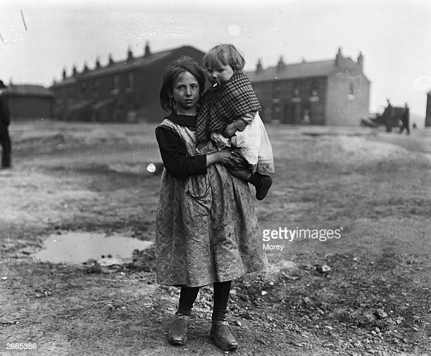 A miner's young daughter carries an even younger child in her arms in Wigan during the coal strike of 1921