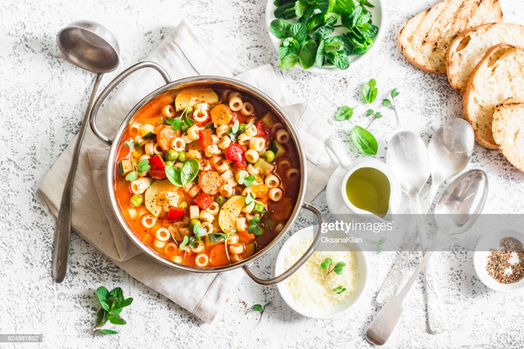 Minestrone soup in a pan on a light table, top view. Italian soup with pasta and seasonal vegetables. Delicious vegetarian food concept. Flat lay : Stock Photo