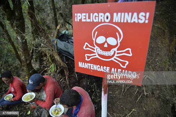 Minesweepers have a meal beside a sign warning about mine hazard after working clearing a minefield laid by guerrillas in La Virgen Carmen de Viboral...