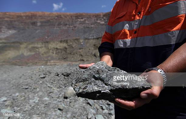A mineworker displays a lump of diamondbearing kimberlite rock from the pit floor in this arranged photograph at the Jwaneng mine operated by the...