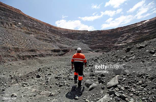 A mineworker walks across diamondbearing kimberlite rock on the pit floor of the Jwaneng mine operated by the Debswana Diamond Co a joint venture...