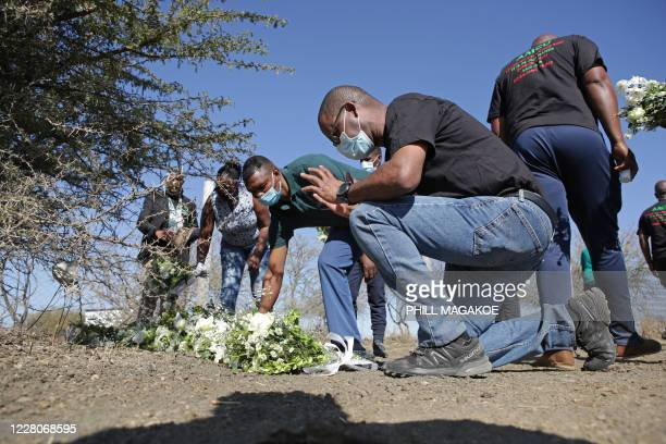 Mineworkers bring flowers as they march to the koppie in Marikana near Rustenburg on August 16, 2020 where striking miners were killed during the...
