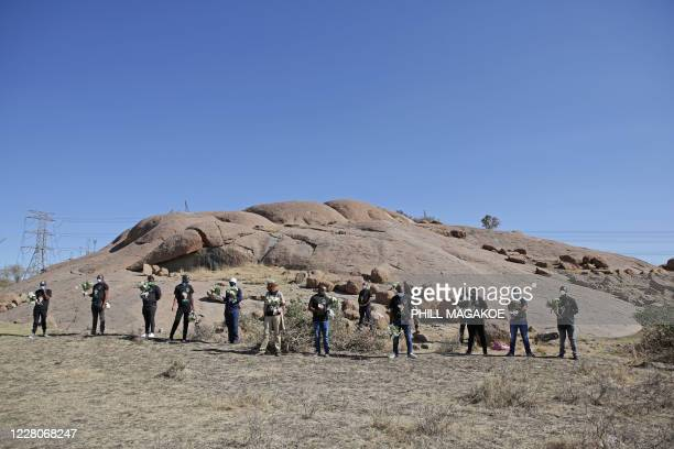 Mineworkers carry flowers as they arrive to the koppie in Marikana near Rustenburg on August 16, 2020 where striking miners were killed during the...