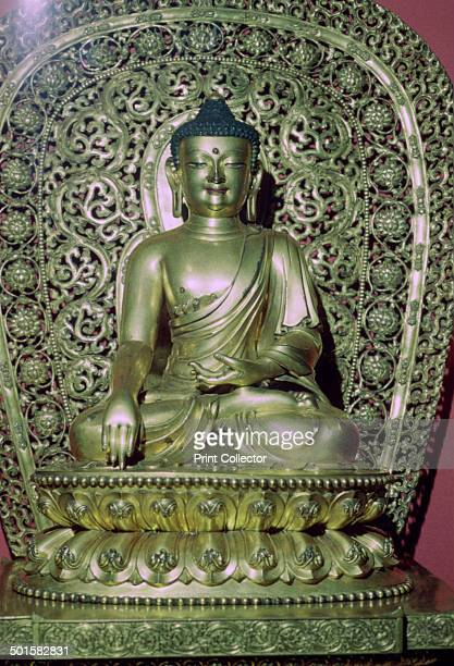 A Ming Dynasty giltbronze seated figure of Shakyamuni Buddha seated on a lotus throne from the British Museum's collection The arched mandola behind...