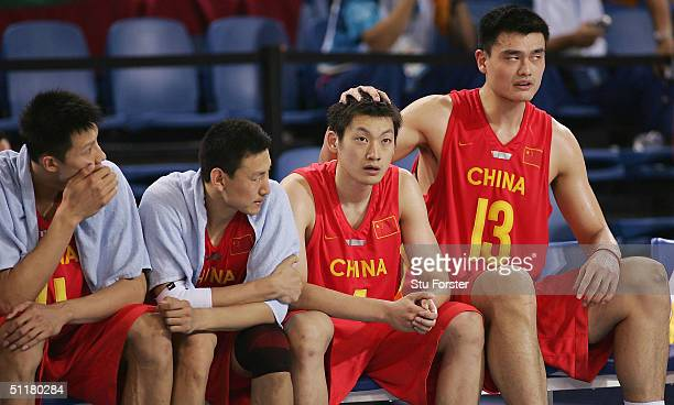 Ming Yao of China consoles Ke Chen of China after having an argument with a fellow player during the men's basketball preliminary game against New...