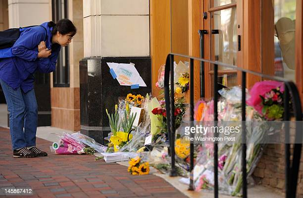 Ming Zhu looks at a makeshift memorial that sits outside the Lululemon Athletica store in Bethesda MD on March 14 2011 after Jayna Murray was killed...