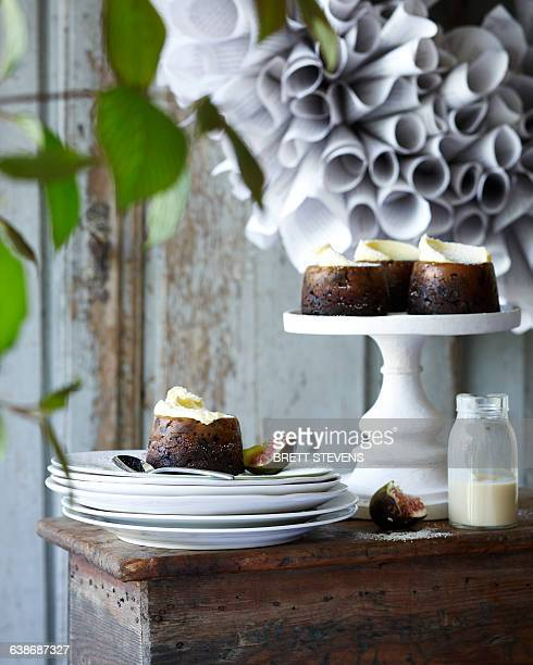 Mini christmas puddings on stack of plates on patio table