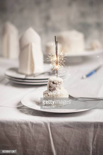 Mini coconut birthday cake with sparklers on plate