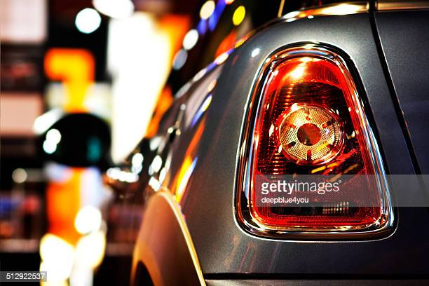 mini cooper vehicle at night at public dealership shopping window - mini cooper stock pictures, royalty-free photos & images