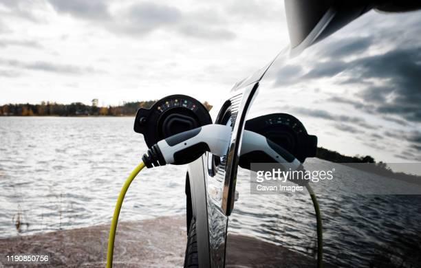 mini electric car charging socket and lead by the beach - electric car fotografías e imágenes de stock
