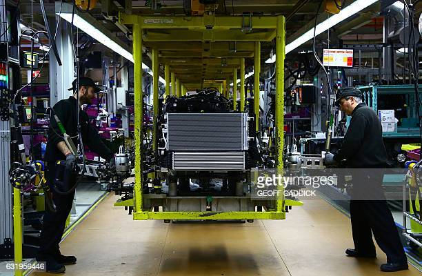 A Mini engine is 'dressed' on the assembly line at the BMW Mini car production plant in Oxford west of London on January 17 2017 / AFP / GEOFF CADDICK