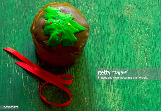 a mini homemade panettone with its red ribbonover a green background. still life. - panettone foto e immagini stock