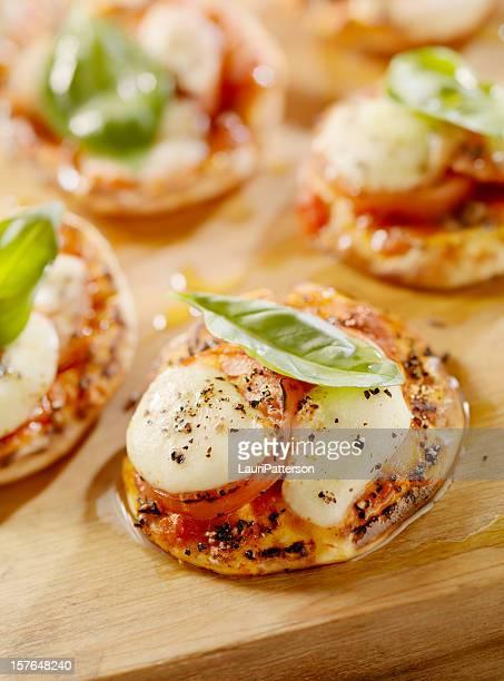 mini pizza margherita sul piatto pane - piccolo foto e immagini stock