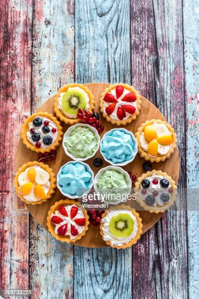 mini pies with whipped cream garnished with different fruits - fruit exotique photos et images de collection