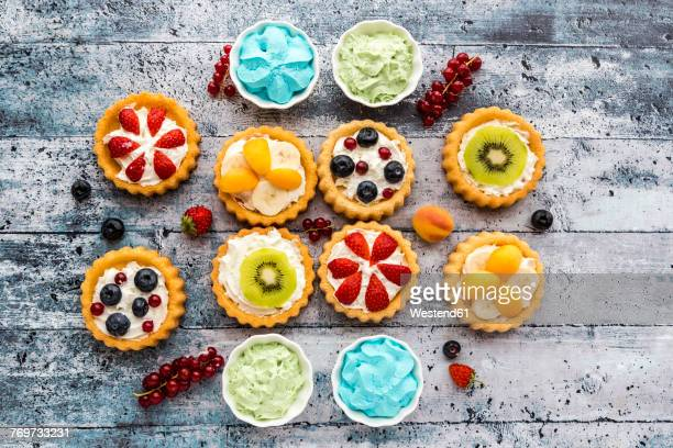 Mini pies with whipped cream garnished with different fruits