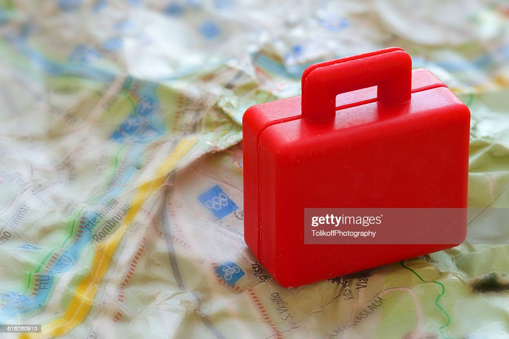Mini red suitcase on a jammed a map. Closeup : Stock Photo