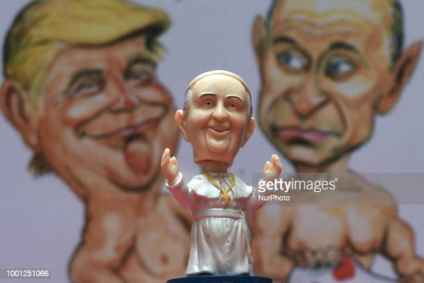 A mini size Pope Francis Bobble head in front of a watercolor caricature which features President Donald Trump and President Vladimir Putin made by...